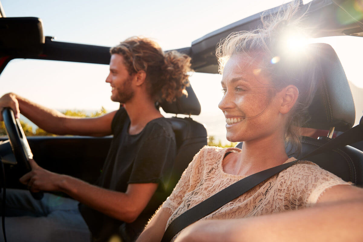 Millennial white couple on a road trip driving in an open top car, backlit, close up