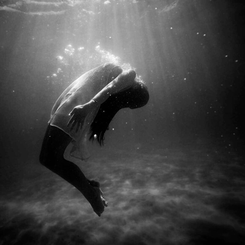 grayscale photo of woman drowning in water